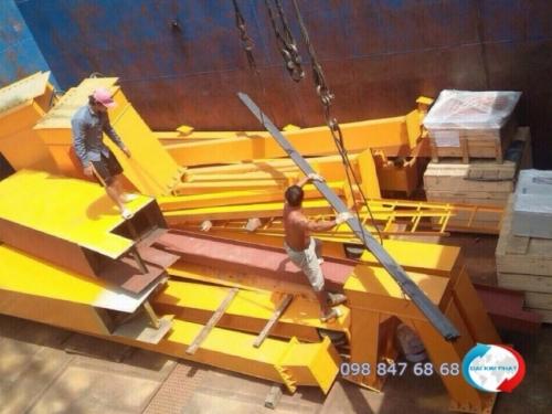 Đội nhân công bốc xếp thực hiện công việc của mình - sắp xếp khung nhà thép tiền chế vào khoang sà lan