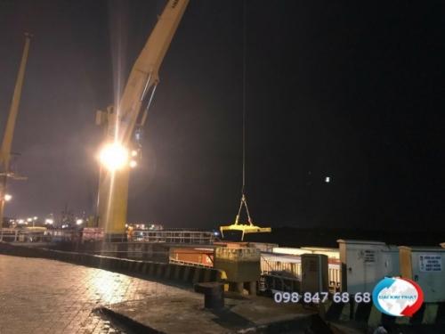 Bốc xếp container xuống lòng sà lan trong đêm tại cảng - hình ảnh khai thác cảng của Dịch Vụ Hải Quan Trọn Gói - XNK Đại Kim Phát